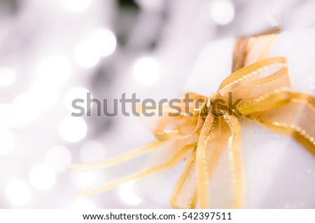 white Christmas gift box  with gold ribbon  and copyspace for your greeting or wishes