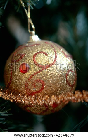 White Christmas ornament with ribbon hanging on a pine tree branch.