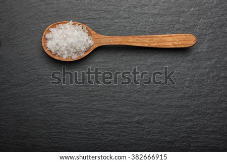 white crystals sea salt on wooden spoon on black stone background, top view