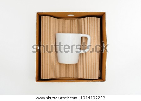 White cup in a box on a white background. Concept of storage, feeling safe, protect, relocation.