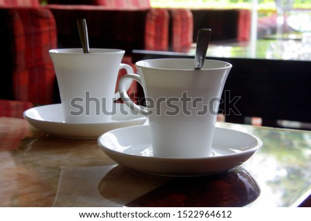 White cup of coffee. A cup of tea. Nice view from the window. Two small cups. China. #1522964612