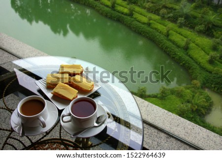 White cup of coffee. A cup of tea. Nice view from the window. Two small cups. China. #1522964639