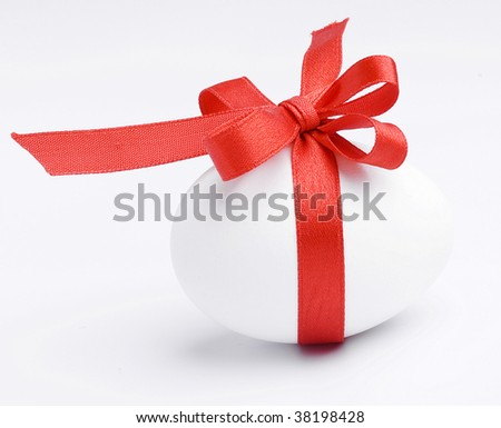 White egg wrapped around with red ribbon  isolated on white background