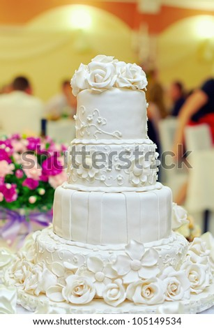 white floral wedding cake on restaurant interior background