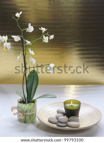 white orchid with candle and massage stones on platter