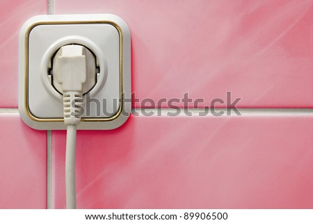 white outlet with a electric plug in a bathroom