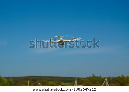 white quadcopter with camera for photo and video shooting flying in the sky