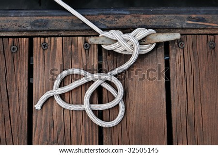 white rope securing boat to wooded dock #32505145