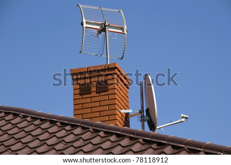 White satellite dish on brown roof