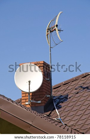 White satellite dish on brown roof - stock photo
