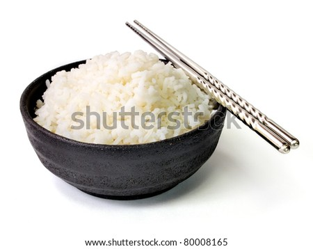 White steamed jasmine rice in black ceramic bowl with silver chopsticks