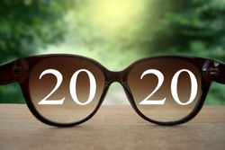 2020 white text with black eye glasses on wooden table over blur autumn landscapes. Business vision happy new year.