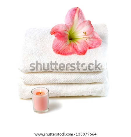 white towels with pink flower and candle isolated on white background