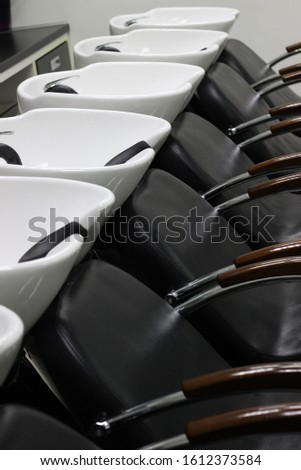 white washbasins for hairdressers in the salon with a black armchair