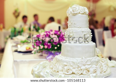 white wedding cake on restaurant interior background