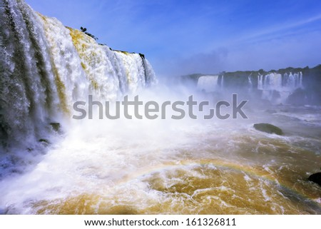 White whipped foam of water and a thin mist over the water. The most high-water waterfall in the world - Iguazu