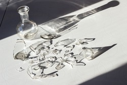 whole and broken decanter on a white table