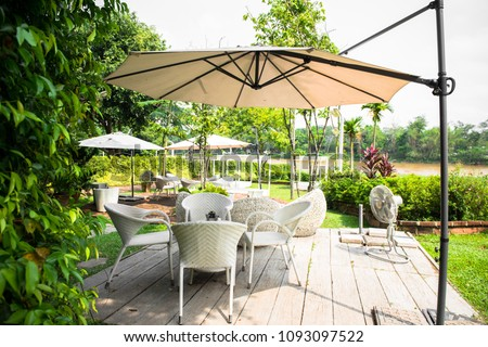 Wicker furniture, outdoor chair set and white umbrella in the garden #1093097522