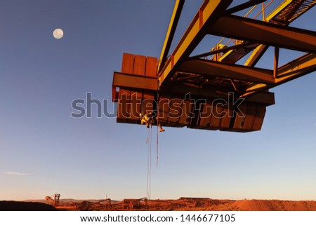 Wide angle concept of industry rope access technician inspector wearing fall body safety harness abseiling working at height inspecting defect of concrete spalling counterweight fall moon background