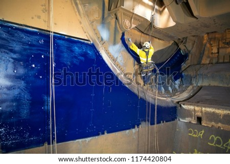 Wide angle picture of rope access painter working at height hanging on twin ropes wearing safety harness chemical mask commencing spray painting in confined space construction site Perth, Australia