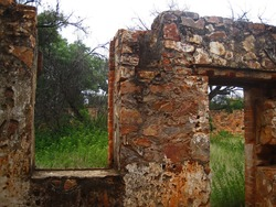 WINDOW AND DOOR OPENING IN STONE WALL OF OLD FORT IN RUINS