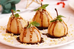 wine poached pears with caramel sauce, decorated background, selective focus, christmas recipe, close up