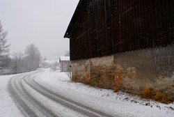 Winter rural landscape. Old house by a snow-covered road. Countryside in Poland. Photo with space for text.