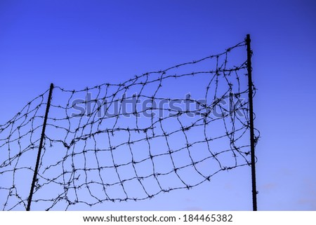 wired fence with barbed wires on blue sky  background