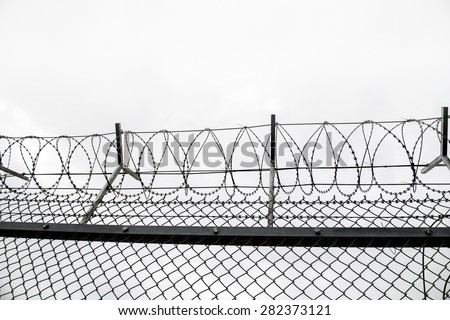 wired fence with barbed wires on cloudy  sky  background
