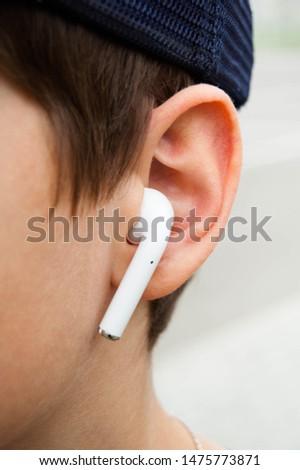 Wireless earphone in ear.  Teenager listens to music.