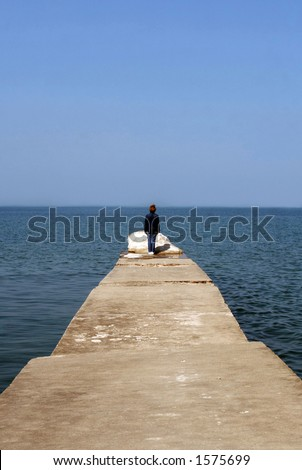 Woman alone on the pier on a beautiful calm day