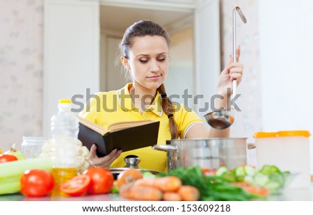woman cooking   food with book at  kitchen