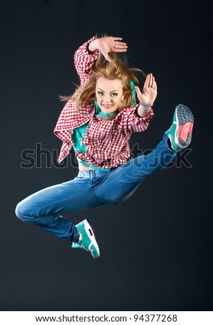 woman dancing hip-hop at studio on grey background