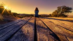105 / 5000 Woman from behind sitting on a wooden floor, contemplating the horizon with sunset in the field.