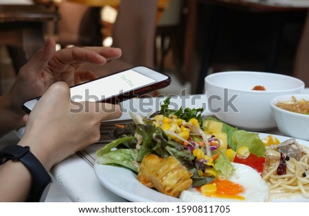 Woman hand looking smartphone for a diet plan which Healthy eating  salad dieting ,fitness and weight loss concept,