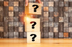 woman  hand placing piece of a big cube with question mark, Question mark cubes.