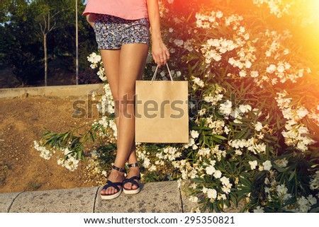 woman holding a paper bag on a background of flowers. flare light, cross process.