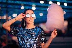 Woman Holding Cotton Candy Dessert in Amusement Park. Female tourist eating fairy floss at funfair enjoying summer vacation
