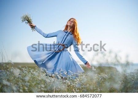 Woman in a chamomile field and holding a bouquet of wildflowers at sunset