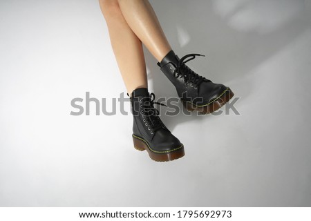 woman in black leather shoes from the new collection on a white background girl's legs in fashionable eco-leather shoes fall-winter 2020. macro photo                               Foto d'archivio ©