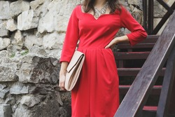 Woman in bright red dress with pale pink large leather clutch in hand. Stylish girl in smart dress on the street.