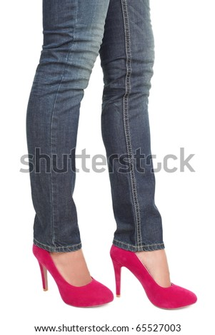 Woman in hot pink red high heels and jeans. closeup of lower half body isolated on white background.