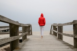 Woman in red jacket standing on the wooden pier, back view