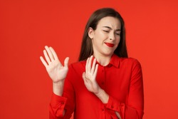 Woman in red shirt gesticulating with hands bright makeup disgust Protest