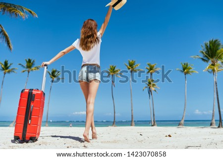 woman in shorts and t-shirt with a red suitcase walks on the sand near the palm trees #1423070858