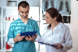Woman in white lab coat and man in medical apparel holding clip-folders. Lifestyle outdoor scene
