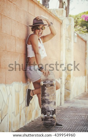 Woman laughing with Skateboard on the street - Shutterstock ID 439954960