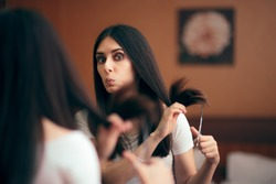 Woman Looking in Mirror Cutting Split Hair Ends. Girl changing looks giving herself a with DIY cut