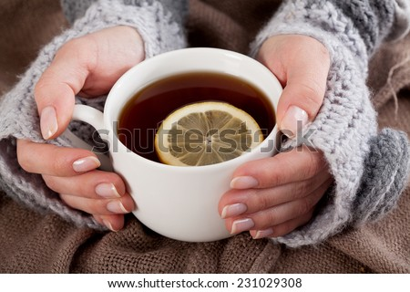 Woman\'s hand holding cup of tea with lemon on a cold day