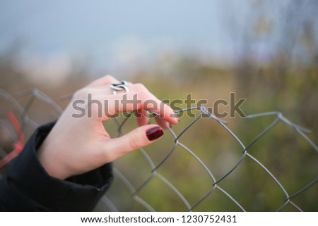 woman's hand on a metal fence. #1230752431